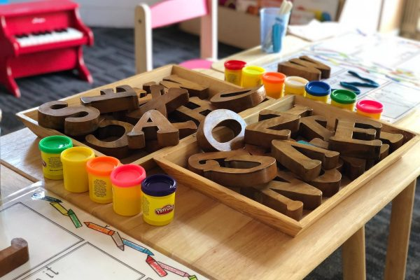 Photo of wooden letters, playdough and other classroom items
