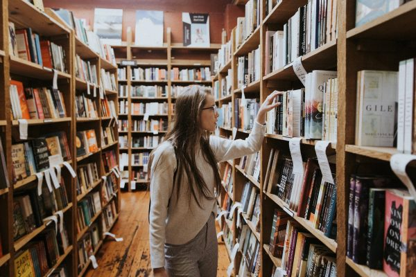 Photo of young woman looking through library shelves
